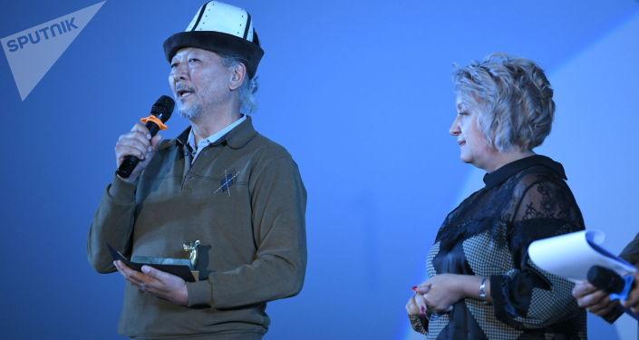 Руководитель информационного агентства и радио Sputnik Кыргызстан Елена Череменина и кинорежиссёр Эрнест Абдыжапаров на национальной кинопремии Ак илбирс в кинотеатре Манас в Бишкеке. 01 октября 2021 года