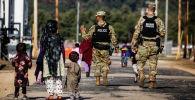Военная полиция США проходит мимо афганских беженцев на базе армии США в Висконсине
