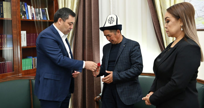 Президент Кыргызстана Садыр Жапаров во время вручения квартиры семье погибшего во время октябрьских событий 2020 года Умутбека Алтынбек уулу
