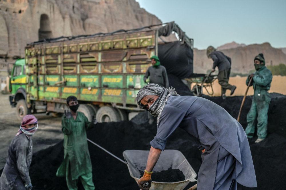 Хазарейские рабочие готовятся грузить уголь в машину в провинции Бамиан