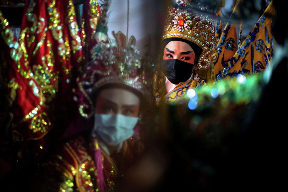 Члены китайской оперной труппы в масках, готовятся к выступлению в храме во время ежегодного вегетарианского фестиваля в Бангкоке (Таиланд). 06 октября 2021 года