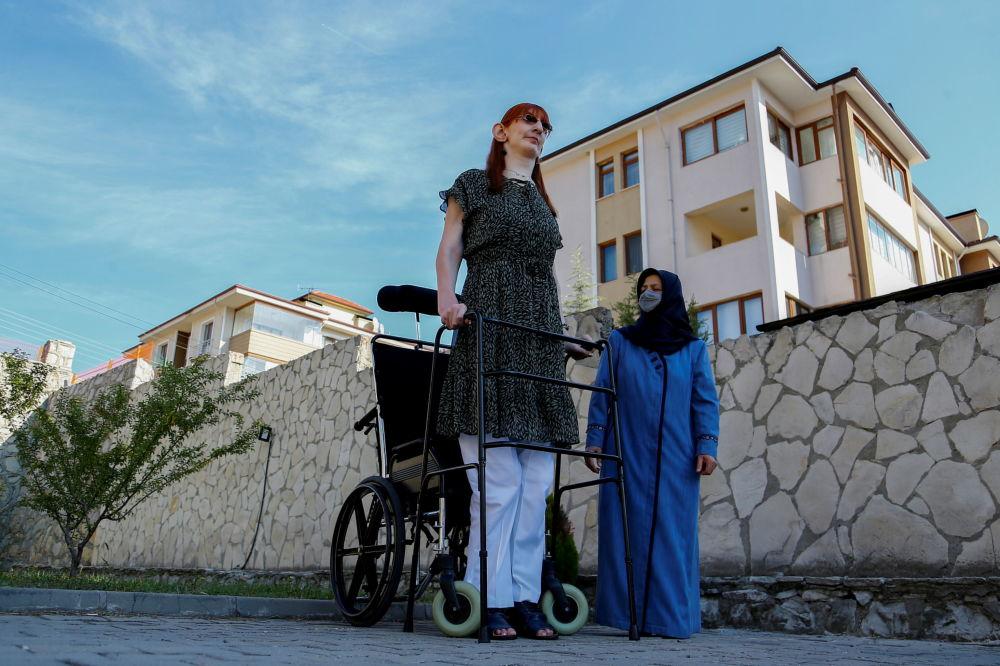 Самая высокая женщина в мире Румейса Гелги позирует со своей матерью во время пресс-конференции перед их домом в Сафранболу (Турция). 14 октября