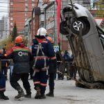 Спасатели муниципальной аварийно-спасательной службы Новосибирска (МАСС) извлекают автомобиль, упавший в провалившийся грунт теплотрассы в Новосибирске.
