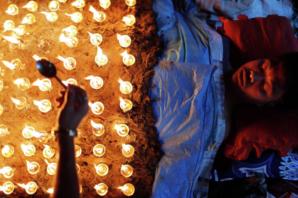 Мужчина лежит неподвижно, пока зажигают масляные лампы над его телом в рамках ритуала празднования десятого и последнего дня фестиваля Дашайн в Бхактапуре. Непал, 15 октября 2021 года
