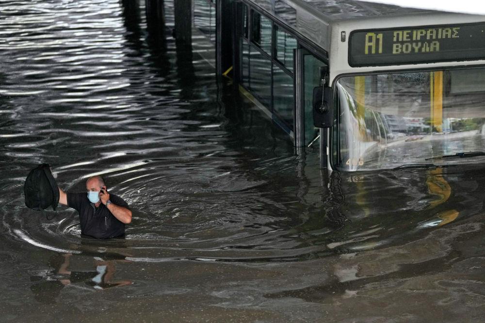 Водитель автобуса разговаривает по мобильному телефону, пробираясь через половодье после эвакуации пассажиров автобуса, застрявшего в затопленном подземном переходе в южных Афинах. 14 октября 2021 года