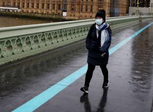 Женщина в маске идет по Вестминстерскому мосту мимо здания Парламента в Лондоне. Архивное фото