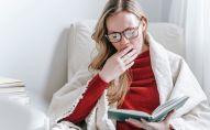 Девушка зевает во время чтения книги. Иллюстративное фото