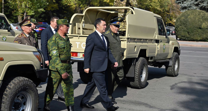 Президент КР Садыр Жапаров и глава ГКНБ на церемонии передачи 40 единиц новой бронированной военной техники пограничной службе ГКНБ