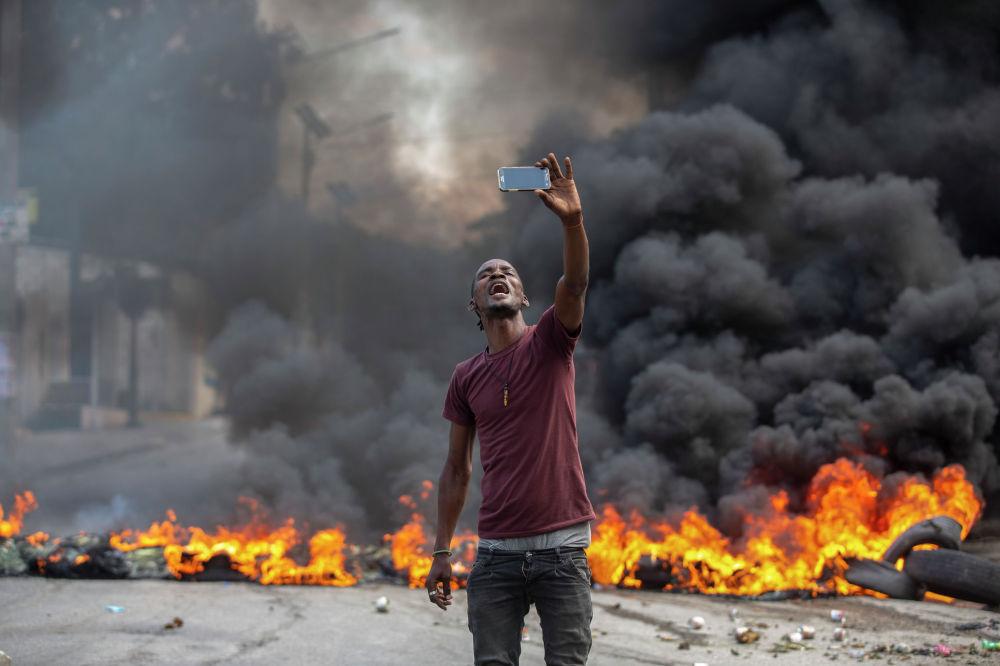 Мужчина фотографируется на фоне горящих шин во время протестов в Порт-о-Пренсе, Гаити. 8 октября 2021 г