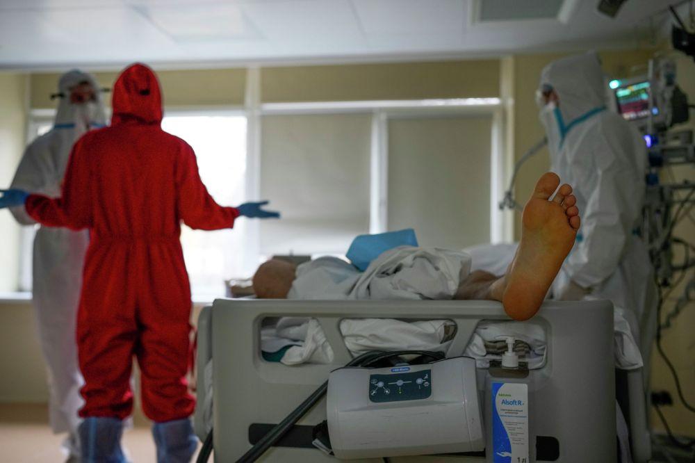 Медицинские работники стоят рядом с пациентом больным COVID-19 в отделении интенсивной терапии инфекционной больницы №23 в Нижнем Новгороде, Россия. 20 октября 2021 года