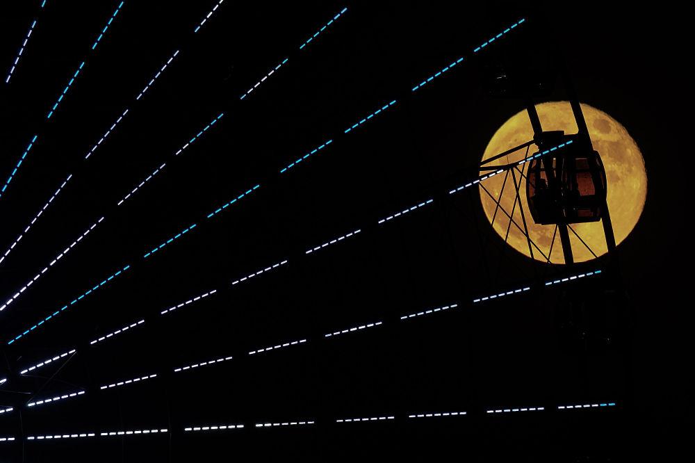 Колесо обозрения на фоне полной луны в Багдаде, Ирак. 21 октября 2021 года