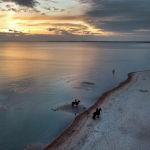 Всадники фотографируются на пляже Балтийского моря в Шарбойце, северная Германия. 17 октября 2021 года