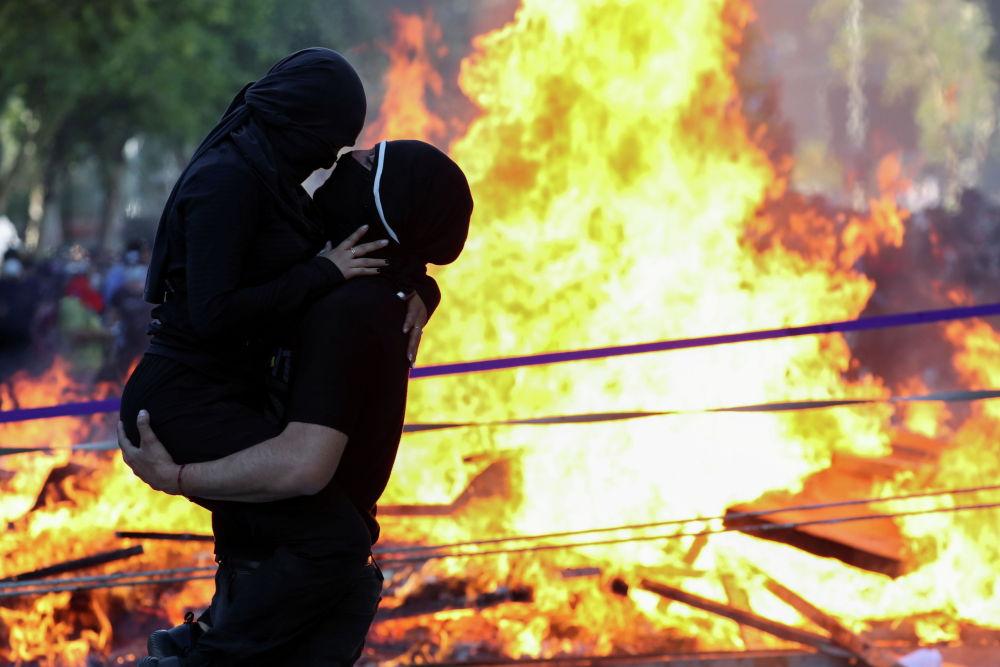 Демонстранты обнимаются во время акции протеста против правительства Чили во вторую годовщину протестов и беспорядков, потрясших столицу в 2019 году, в Сантьяго, Чили. 18 октября 2021 года