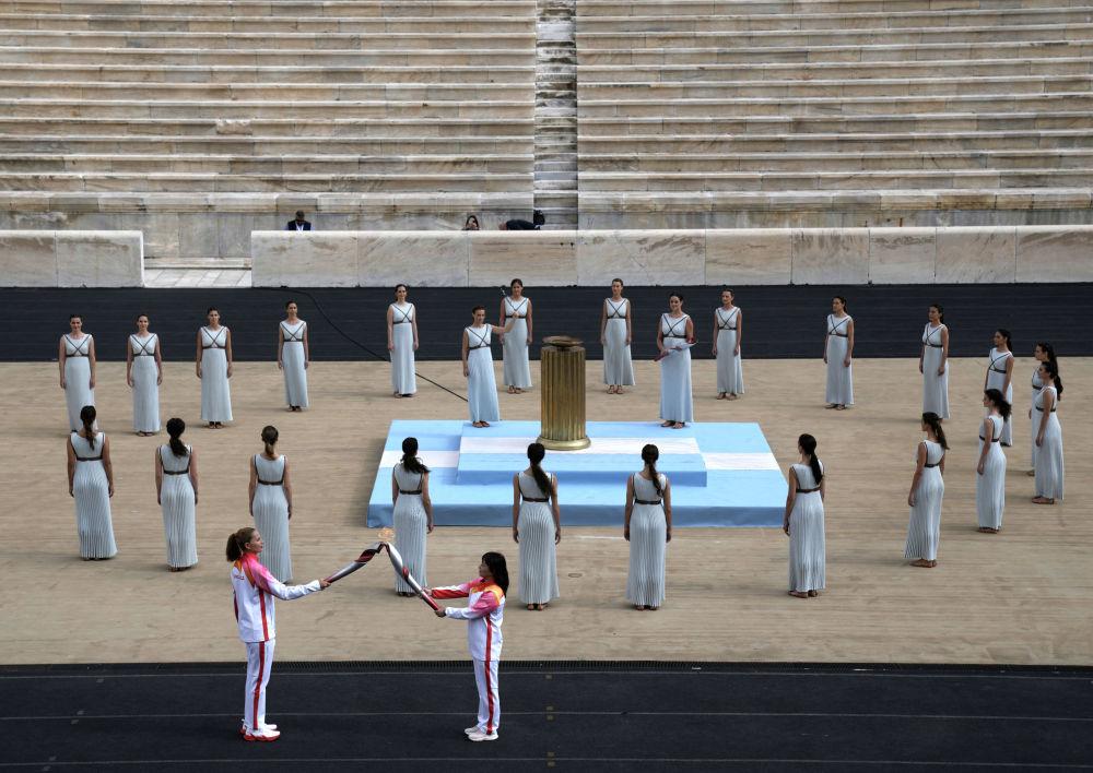 Олимпийская чемпионка Греции по водному поло Эви Мораитиду (слева) передает факел олимпийской чемпионке Китая по лыжным гонкам Ли Нине во время церемонии передачи олимпийского огня на стадионе Панатинаикос в Афинах, Греция. 19 октября 2021 года