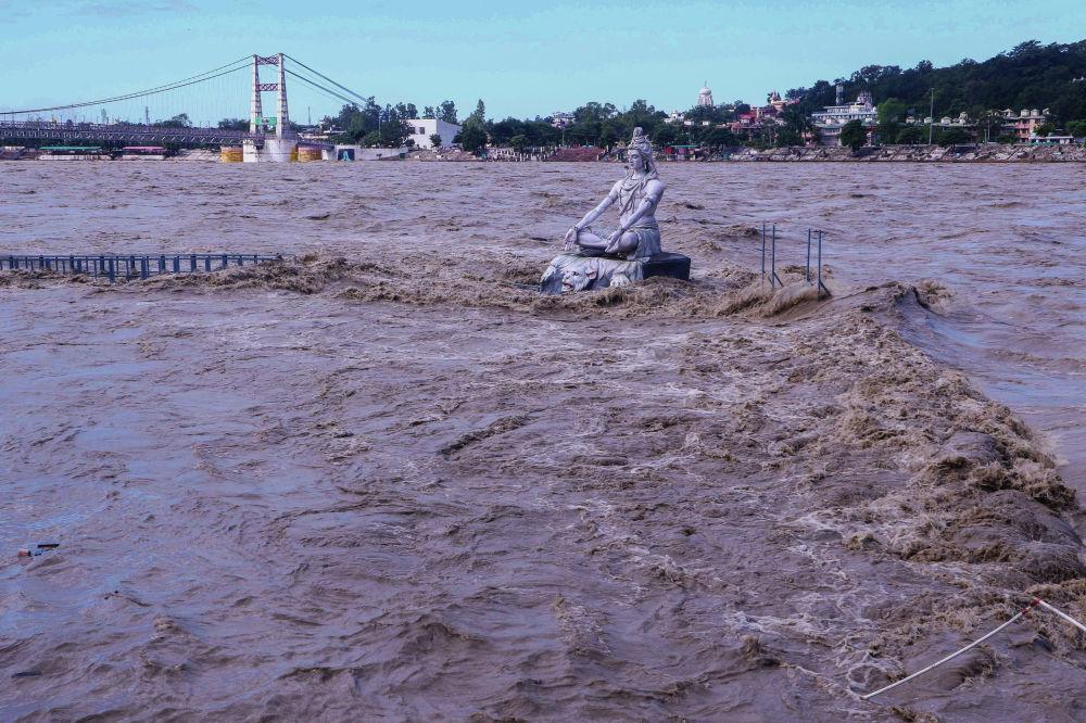 Статуя индуистского бога Шивы на фоне поднявшегося уровня воды в реке Ганг после непрекращающихся дождей в штате Утраханд, Индия. 19 октября 2021 года