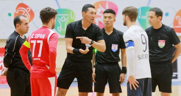 Кыргызстанские судьи по футзалу Элдияр Келдибеков и Талант Раимбердиев во время судейства финального матча профессиональной лиги Таджикистана. 25 октября 2021 года