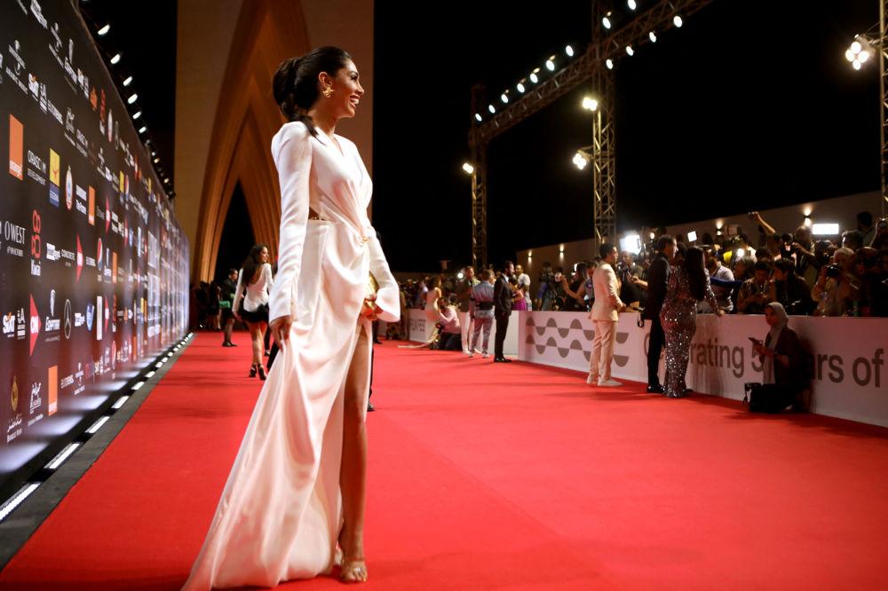 Кызыл килемде сүрөткө түшүп жаткан египеттик модель Энджи Кеван