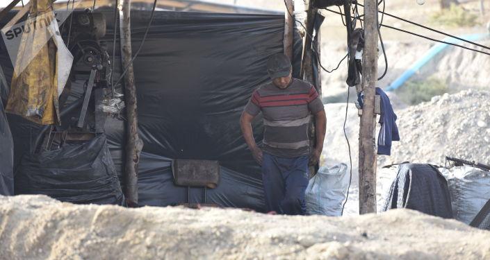 Рабочий во время добычи угля на заброшенной шахте в городе Кызыл-Кия