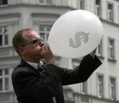Человек в костюме надувает воздушный шар со значком американского доллара. Архивное фото