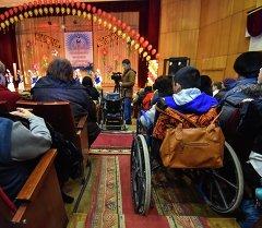 Дети-инвалиды и их родители смотрят выступление танцевальной группы. Архивное фото