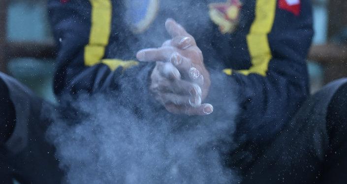 Спортсмен перед восхождением натирает руки тальком. Архивное фото