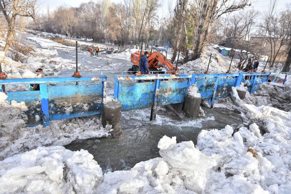 Сотрудники МЧС расчищают реку от шуги.