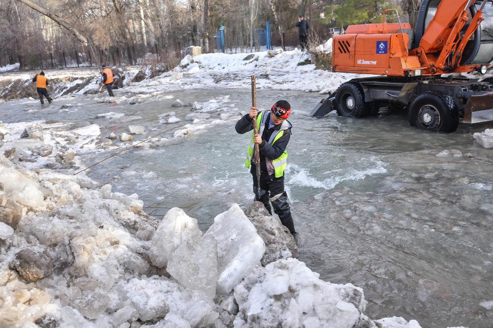 Рабочие раскалывают лед вручную, чтобы вода как можно скорее вернулась в русло.