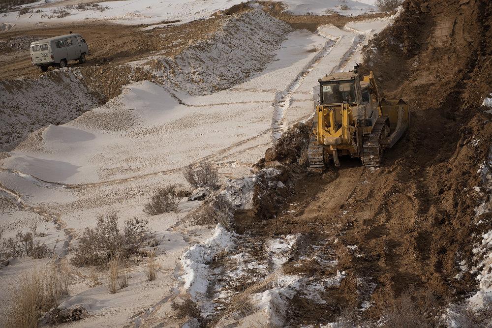 Трактора выравнивают землю для заливки бетона.