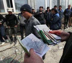 Россиянын Федералдык миграциялык кызматчысы документ карап аткан кези. Архив