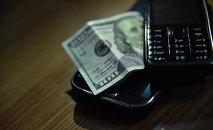 Деньги с телефоном. Архивное фото