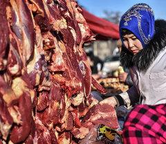 Женщина за покупкой мяса на ярмарке. Архивное фото