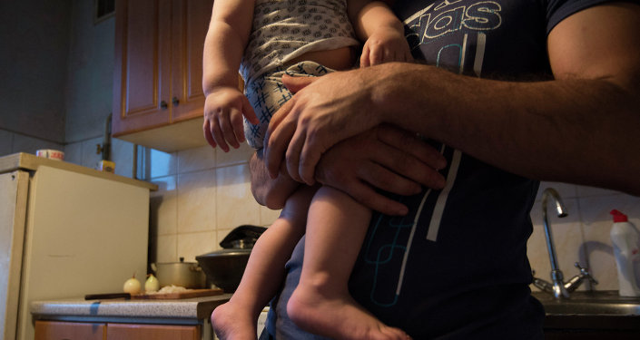 Мужчина с ребенком на руках. Архивное фото