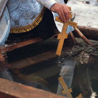 Перед нырянием в воду батюшка освящает Иордань. Архивное фото