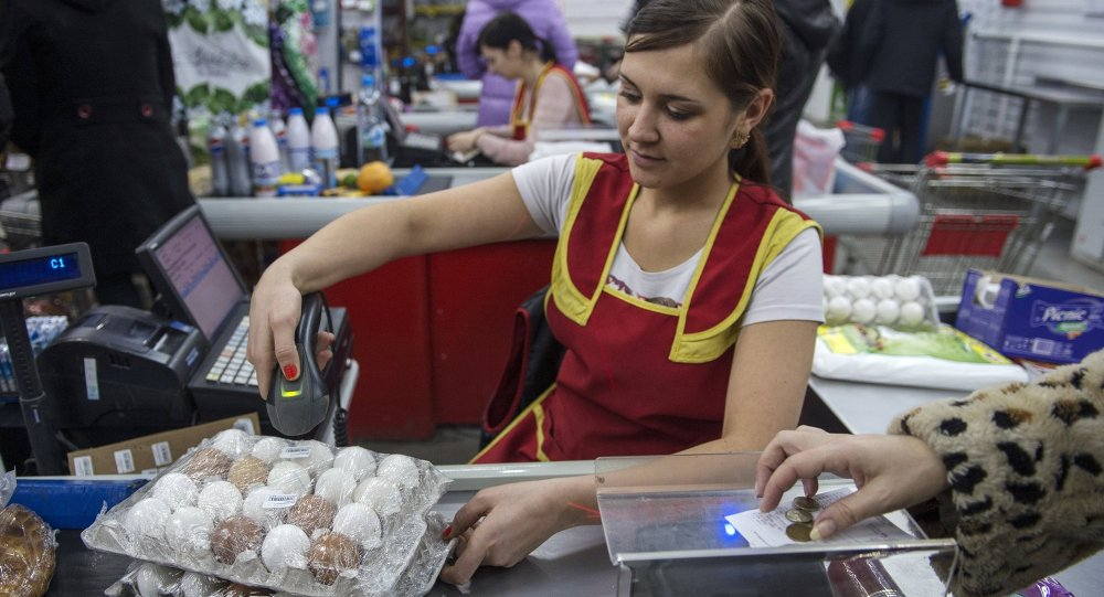 Кассир пробивает упаковку куриных яиц в магазине