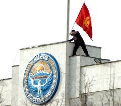 Кыргызстандын желегин Ак үйдүн крышасына орнотуп жаткан митингдин катышуучусу. Архив