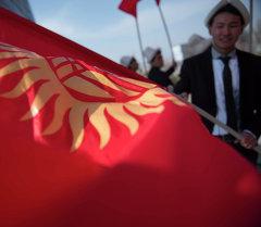 Кыргызстандын желегин кармаган жигит. Архив