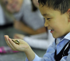 Ребенок с монетами в руке. Архивное фото