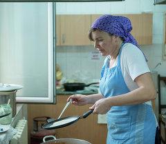 Женщина готовит еду на кухне. Архивное фото