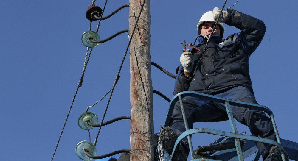 Электрик снимает провода со старой опоры линии электропередачи. Архивное фото