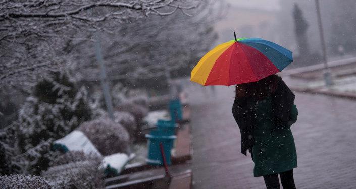Прохожий с зонтиком во время снегопада. Архивное фото