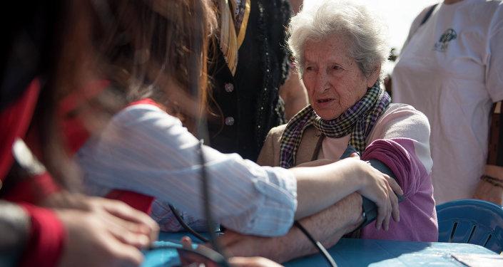 Измерение давления у пожилой женщины. Архивное фото