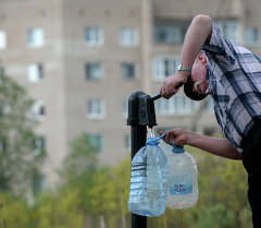 Мужчина набирает воду из колонки. Архивное фото