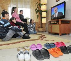 Телевизор көрүп жаткан адамдар. Архив