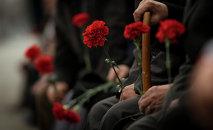 Люди с гвоздиками в руках на похоронах. Архивное фото