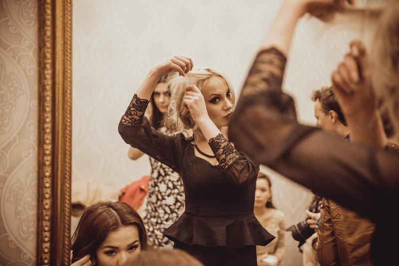 Финалист конкурса красоты Красавица Кыргызстана 2015 приводит в порядок прическу перед зеркалом.