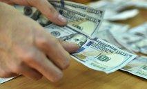 Мужчина считает долларовые купюры США. Архивное фото