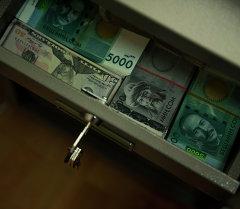 Доллары и сомы в сейфе. Архивное фото