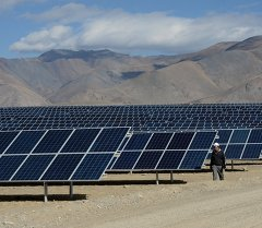 Мастер осматривает солнечные батареи на солнечной электростанции. Архивное фото