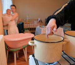 Молодая семья греет воду на газовой плите. Архивное фото