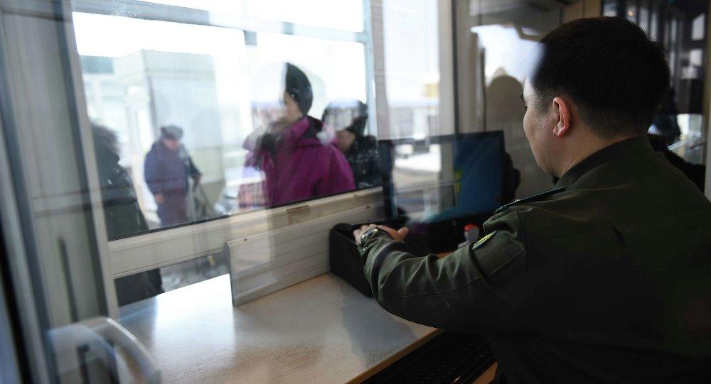 Сотрудник контрольно пропускного пункта кыргызско-казахской границы проверяет документы у граждан. Архивное фото